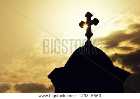 Chapel or church roof with a cross in silhouette against a sunburst at sunrise or sunset in an atmospheric spiritual skyscape.