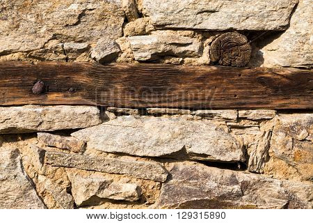 Close up background texture and pattern of an old weathered irregular shaped natural stone or rock wall with wooden parallel beam.
