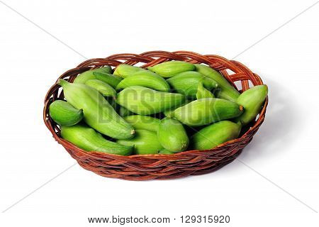 small basket with many small green unripe fruits of caigua appropriate for the marinating on white background