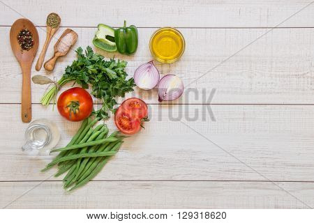 Left fresh vegetables ready to cook tomatoes peppers green beans onions parsley spices in wooden spoons on light wood background right empty space. Horizontal.Top view.