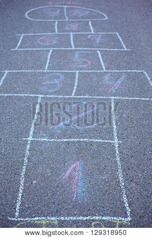 Hopscotch drawn on asphalt. Soft focus on number 1.