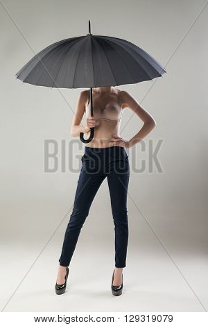 Unrecognizable young woman in trousers and bra posing with black umbrella against of white background