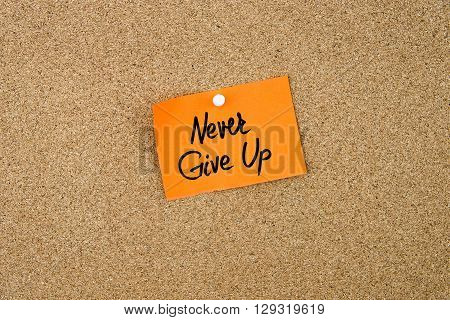 Never Give Up Written On Orange Paper Note
