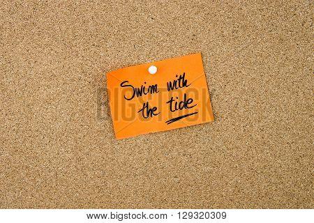 Swim With The Tide Written On Orange Paper Note
