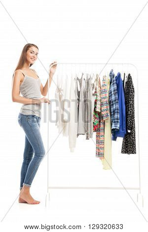Beautiful young brunette smiling at camera while standing near hanger with different clothes.Studio shot