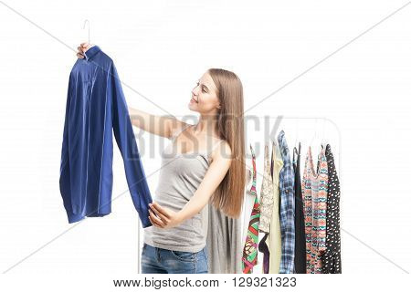 Portrait of satisfied young woman looking at blue man's shirt