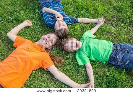 Three smiling kids lying down together on green grass meadow