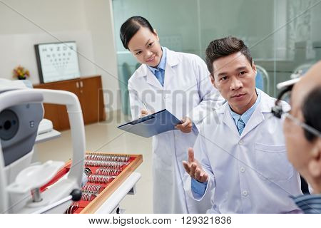Nurse taking notes when ophthalmologist talking to patient