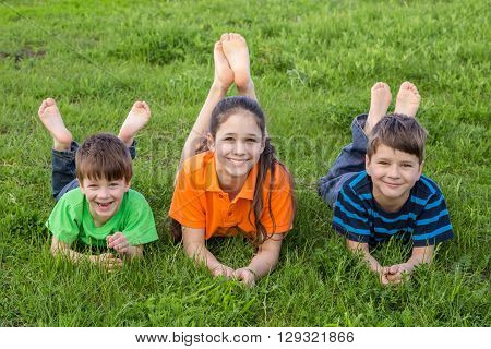 Three smiling kids lying together on spring green grass meadow