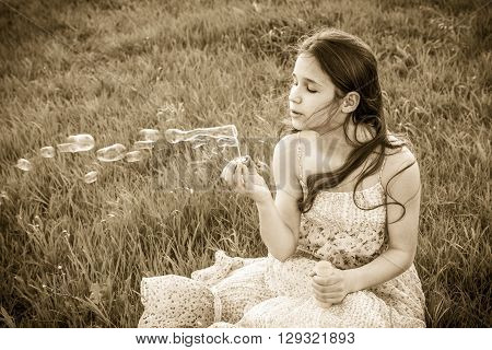 Girl blowing up the soap bubbles sitting on grass
