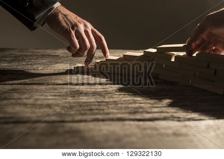 Closeup view of businessman arranging wooden pegs in to a staircase like structure for his colleague to walk his fingers up the steps. Conceptual of business cooperation vision and success.