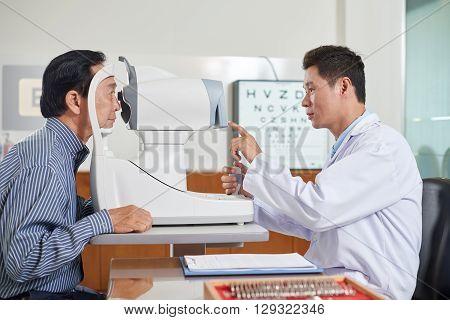 Doctor explaining senior man how eye test equipment works