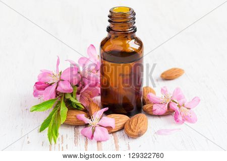 small bottle of almond oil almonds and flowers.