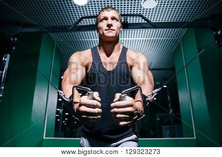 Portrait of young bodybuilder doing exercise with cable ropes on chest