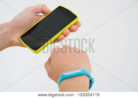 Women's Hands With A Sports Bracelet And Smart Phone Close Up On A White Background