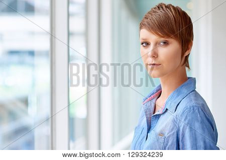Portrait of a modern young woman looking at the camera with a keen and serious expression, in a corridor with bright natural light