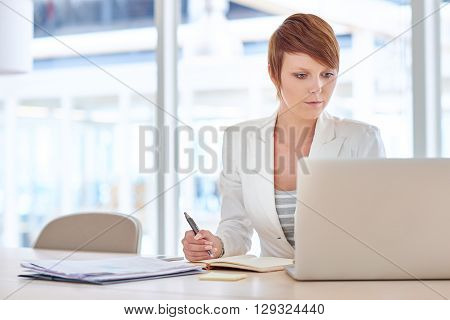 Pretty young female business executive sitting at her desk in a brightly lit office, reading something on the screen of her laptop with paperwork next to her