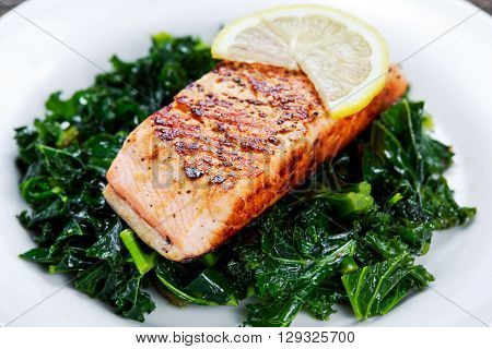 Pan fried Salmon Served with Kale on plate.