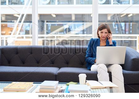 Attractive businesswoman sitting on a couch in a modern office space, holding her mobile phone to her ear while looking at the screen of her laptop computer