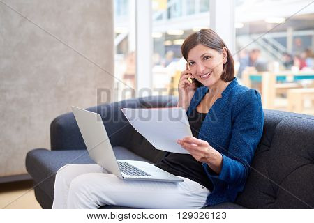 Attractive young businesswoman sitting on an office couch smiling at the camera, while holding some paperwork and her phone to her ear, with her laptop computer on her lap