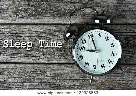 Black alarm clock on the rusty wooden table with word Sleep Time