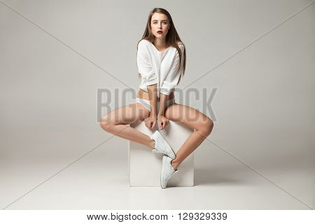 Portrait of beautiful young long-haired woman with bare legs in white undies, sweater and sneakers on white cube.Studio shot.