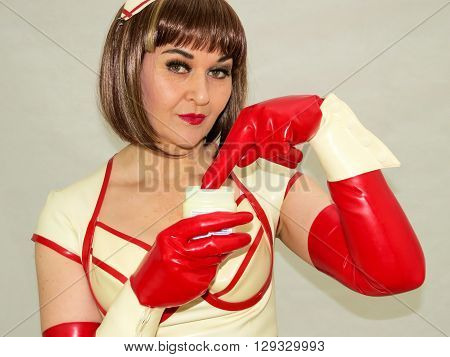 Attractive woman role playing a nurse wearing PVC and dipping fingers in a jar.