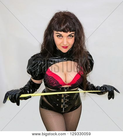 Attractive dominatrix holding a whip in black and red PVC outfit.