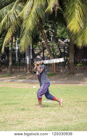 MUMBAI, INDIA - OCTOBER 10, 2015: Man playing cricket in the central park at Mumbai. Cricket is the most popular sport in India. History of cricket in India is based on the existence and development of the British Raj.