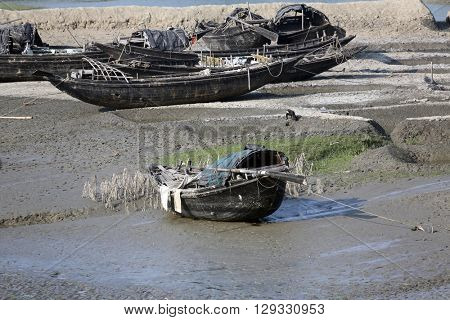 CANNING TOWN, WEST BENGAL, INDIA - FEBRUARY 13: Boats of fishermen stranded in the mud at low tide on the river Malta near Canning Town, India on February 13, 2014.