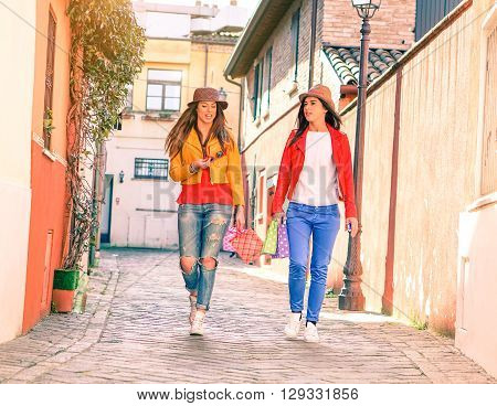 Two young women walking in old city alleyway holding shoppers - Tourists girlfriends talking and gesturing after shopping day - Concept of female friendship and pleasant moment together on holiday