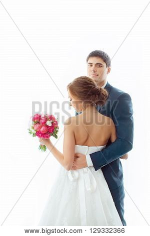 Happy wedding couple in love. Beautiful bride in white dress with brides bouquet and handsome groom in blue suit standing and embracing each other and looking to the camera indoors at home against big window, white bright background