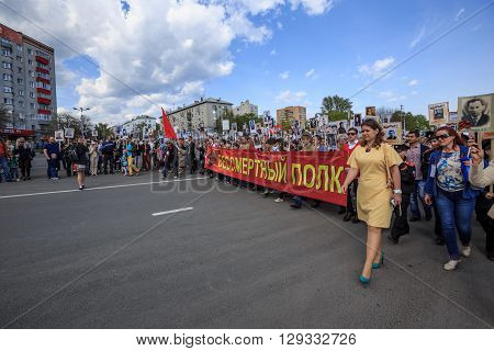 ULYANOVSK, RUSSIA - MAY 9, 2016: People hold red banner of Immortal regiment and portraits of their relatives on 9 May, 2016 in Ulyanovsk, Russia