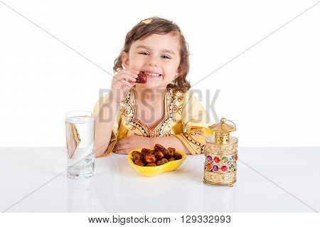 Young Muslim girl eating dates for brakfast in Ramadan - sitting on a table with water , dates , Quran, and Ramadan lantern
