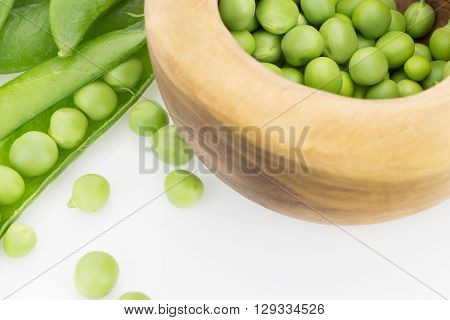 Fresh Green Pea Pods And Peas In Wooden Bowl Closeup, On White Background