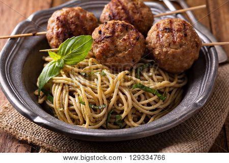 Turkey meatballs on wooden skewers with pesto pasta