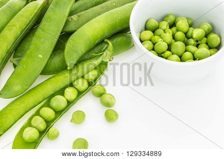 Fresh Green Pea Pods And Peas In Bowl, On White Background