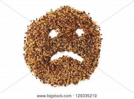 A pile of crushed red pepper flakes showing a sad face depicting heartburn or indigestion.