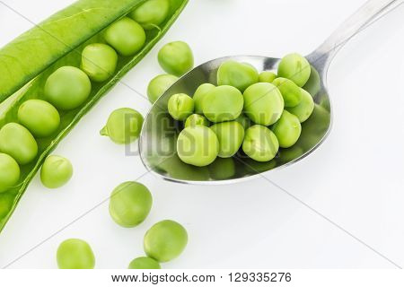 Fresh Green Peas In Spoon Closeup And A Pea Pod, On White Background