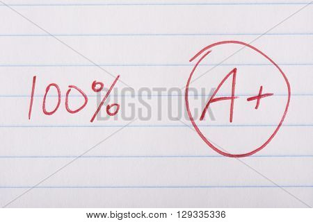 A plus (A+) grade with 100 percent written in red pen on notebook paper.
