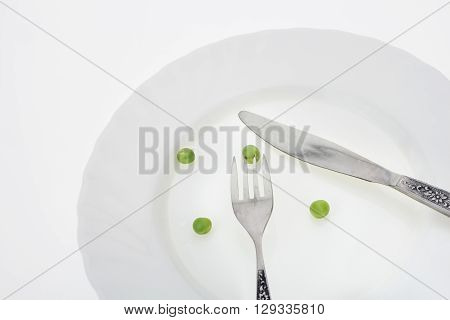 Fresh green peas on plate with fork and knife closeup on white background