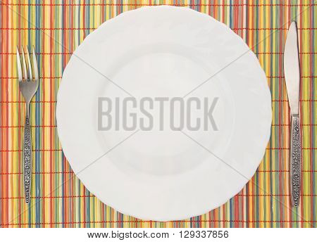 White Empty Plate With Fork And Knife On Colorful Bamboo Placemat