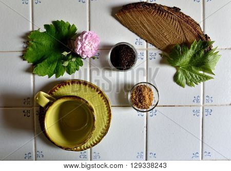 Little cup with cane sugar, coffee powder, pink rose, green leaf and part of wood