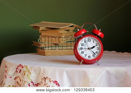 Red retro alarm clock on table with white tablecloth with lace. In the background a stack of books.