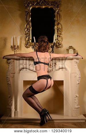 alluring young woman in black sexy lingerie posing in antique interior