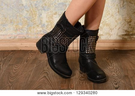 autumn black women's boots in the straps and rivets dressed the girl standing on the wooden floor near the wall