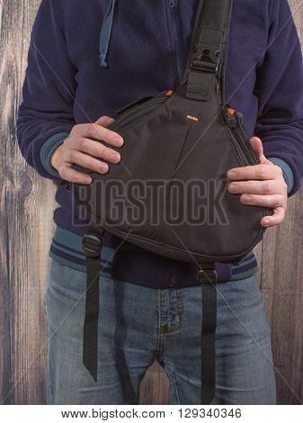 photographer holds the bag for the camera on woooden background