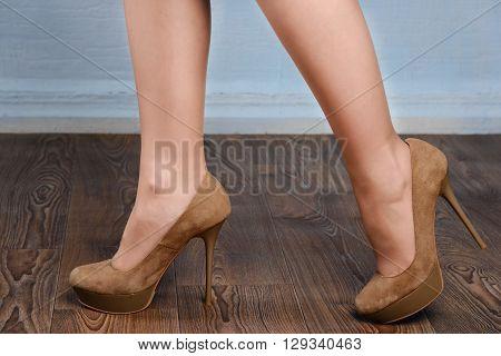 Girl in beige suede high-heeled shoes on the wooden floor