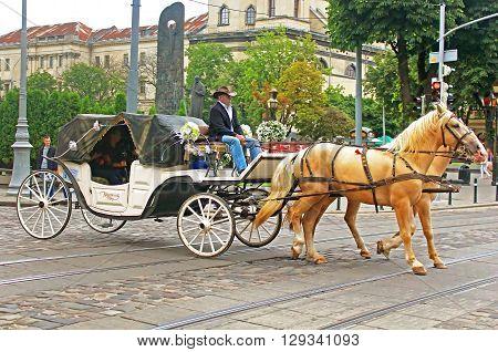 LVIV, UKRAINE - JULY 17, 2015: Tourist brougham with people on the streets in historical city center, Lviv, Ukraine