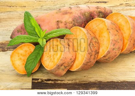 Fresh Sweet Potatoes Whole And Sliced , On Wooden Background